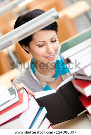 Reading book female student surrounded with piles of books sitting at the desk at the library. Knowledge concept - stock photo