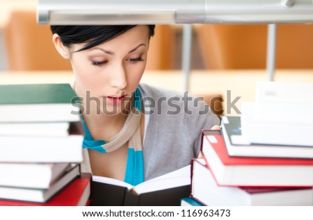 Reading book female student surrounded with piles of books sitting at the desk at the library. Academic achievement - stock photo