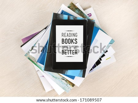 Reading books makes you better - text on a screen of electronic book on top of a pile of books and magazines. Concept of learning new knowledge, self improvement and development of mental abilities - stock photo