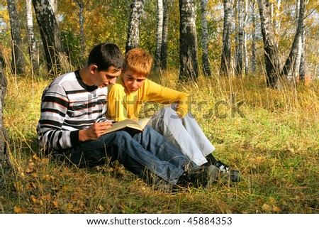 reading boys sit in autumn forest with a book - stock photo