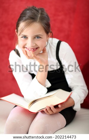Reading Classroom - girl reading a book .Joyful girl reading a book sitting on the orange chair  - stock photo