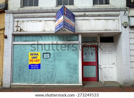 Reading, England - April 23, 2015: Empty retail unit with a real estate sign in Reading, England. In 2014 one in three high street properties in Britain were empty according to The Local Data Company - stock photo