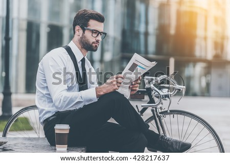 Reading fresh news. Side view of young businessman reading newspaper while sitting near his bicycle with office building in the background - stock photo