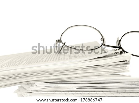 Reading glasses on stack of papers held together with bulldog paper clip. Blurred text. Horizontal, isolated with room for text, copy space. Office job stress concept. Sepia tint. - stock photo