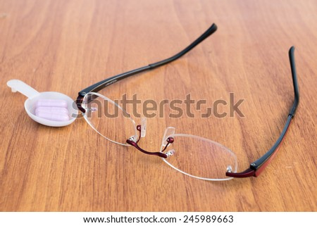 Reading glasses on the wood table with drug - stock photo