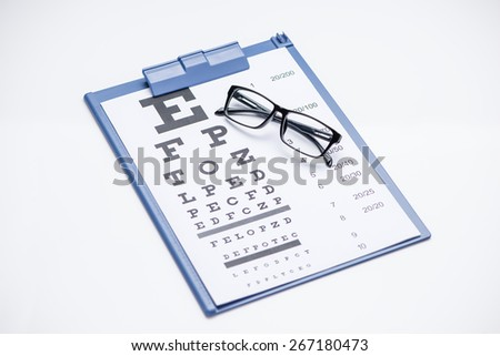 Reading glasses with eye chart on blue clipboard isolated over white. Close up eye check concept  - stock photo