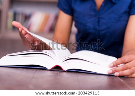 Reading her favorite book. Close-up of African female student reading a book while lying on the floor in library - stock photo