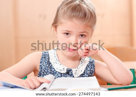 Reading is sad .Little pretty girl is sad while reading book during classes. - stock photo