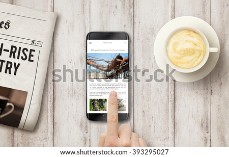 Reading news article on the phone during coffee time. Newspapers, coffee on the wooden table with top view. - stock photo
