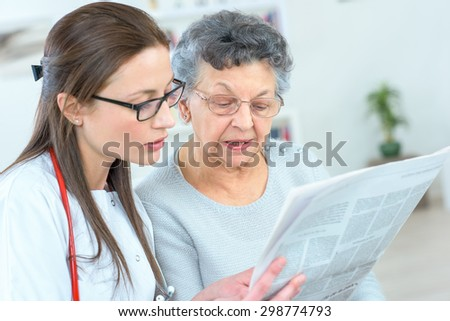 Reading newspaper with an old lady - stock photo