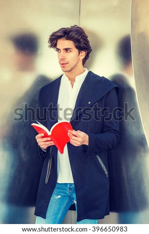 Reading outside. American college student wearing fashionable long coat, jeans, standing against metal wall in New York, opening red book, looking away, reading, thinking. Instagram filtered effect.  - stock photo