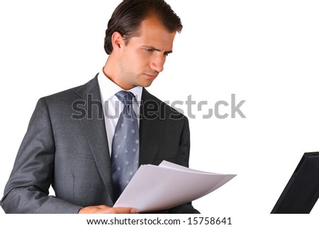 Reading papers and comparing them to the info on the computer screen - stock photo