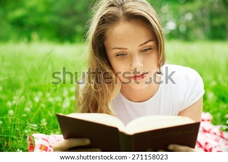 Reading. Pretty girl on a grass looking over the book - stock photo