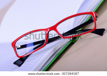Reading red eyeglasses and paper notebook close-up on a light background - stock photo