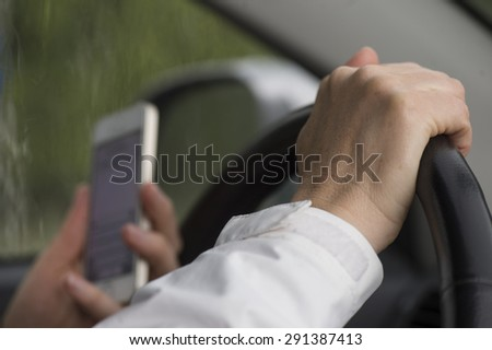 Reading text message while driving a car - stock photo