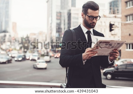 Reading the latest news. Confident young man in full suit reading newspaper while standing outdoors with cityscape in the background - stock photo