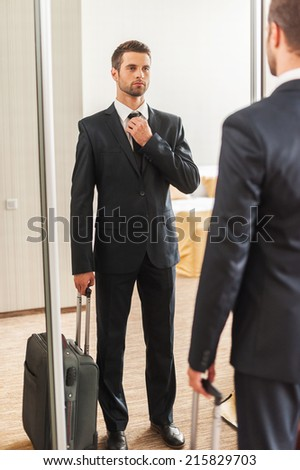 Ready for business trip. Confident young man in formalwear adjusting his necktie while standing against mirror in hotel room - stock photo