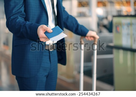 Ready for check-in. Cropped image of a handsome young businessman in suit stretching out his ticket while standing in front of the airline check in counter in the airport - stock photo