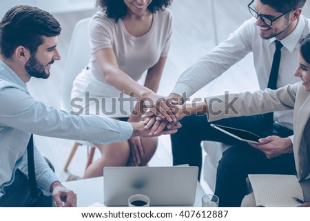 Ready for new achievements every day. Close-up part of top view of group of four young people holding hands and showing their unity with smile while sitting on the couch at office  - stock photo