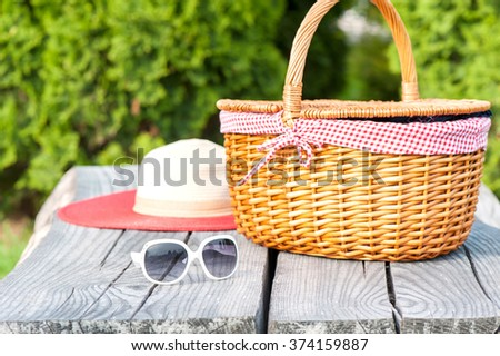 Ready for summer holidays. White sunglasses summer hat and wicker basket on wooden table background. Multicolored vibrant outdoors horizontal image. - stock photo