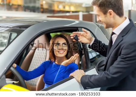 Ready for test drive. Handsome young car salesman giving key to young beautiful woman  - stock photo