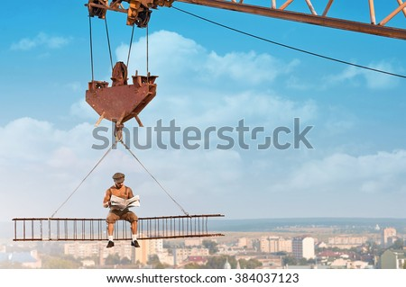 Ready for the news. Fearless old fashioned builder man reading a newspaper sitting on a crossbar hanging on a crane above the city - stock photo