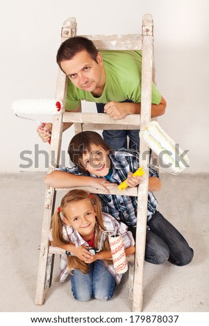 Ready for the paint job - father and kids with painting utensils - stock photo