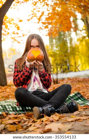 Ready for trick or treat? Shot of a young girl sitting in the forest hiding her face behind a pumpkin with a carved heart - stock photo