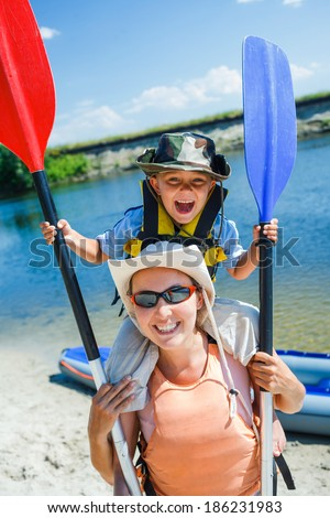 Ready kayaking. Mother and son with a kayak on the river, enjoying a lovely summer day - stock photo