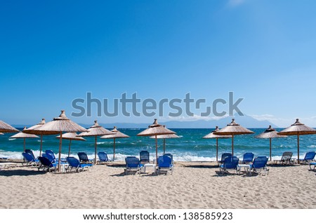 Ready parasols and armchairs on the beach with sea and sky in the background - stock photo