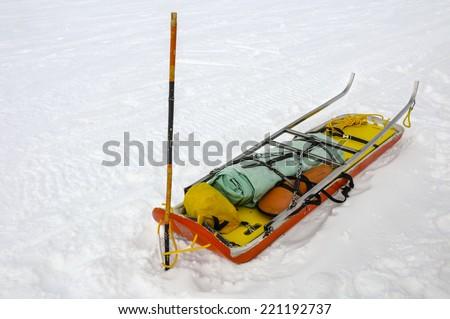 Ready ski patrol sled on  snow - stock photo