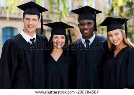Ready to bright future. Four college graduates in graduation gowns standing close to each other and smiling - stock photo