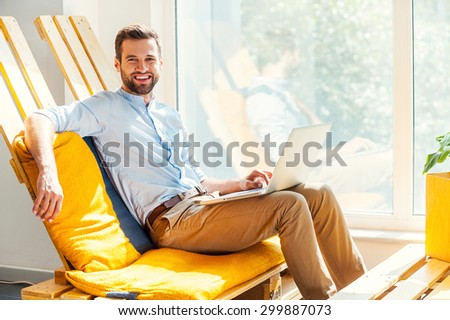 Ready to do business. Happy young man working on laptop and looking at camera while sitting inthe rest area of the office - stock photo