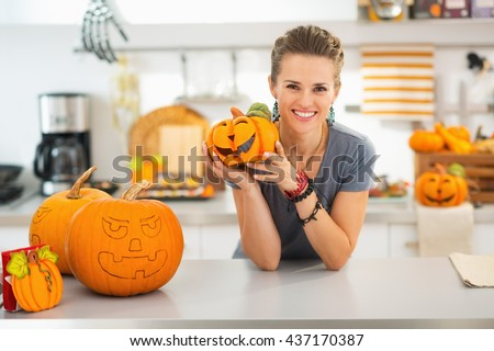 Ready to halloween invasion. Smiling young woman showing ceramic pumpkin in halloween decorated kitchen. - stock photo