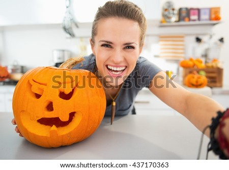 Ready to halloween invasion. Smiling young woman taking selfie in halloween decorated kitchen. - stock photo