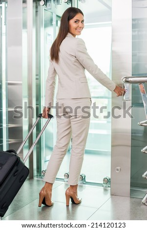 Ready to new business trip. Rear view of confident young businesswoman in formalwear pushing button while standing near elevator entrance - stock photo