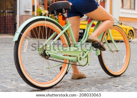 Ready to ride. Close-up of young woman riding bicycle along the street - stock photo