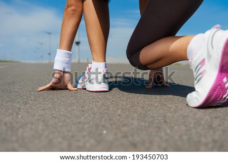 Ready to run.  Close-up image of woman in sports shoes standing in starting line  - stock photo