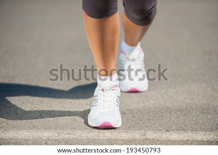 Ready to run.  Close-up image of woman in sports shoes walking  - stock photo