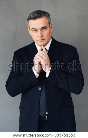 Ready to start new business. Mature businessman holding hands on chin and looking at camera while standing against grey background - stock photo