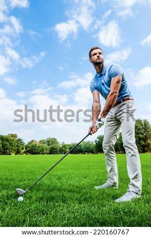 Ready to strike. Low angle view of young man playing golf while standing on green - stock photo