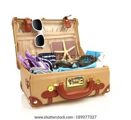 Ready to travel open suitcase with summer equipment isolated  - stock photo