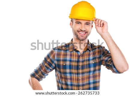 Ready to work. Confident young male carpenter adjusting his hardhat and smiling while standing against white background  - stock photo