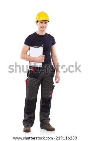 Ready to work. Construction worker in yellow helmet standing and holding clipboard under his arm.  Full length studio shot isolated on white. - stock photo