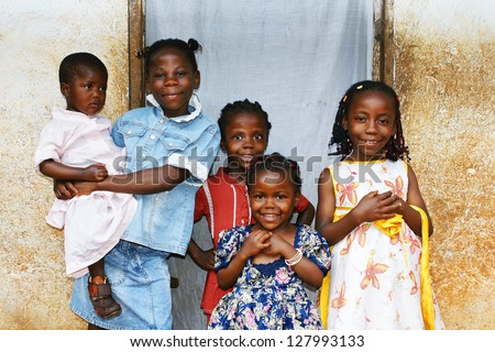Real candid family photo of five cute and sweet black African sisters or girls, all smiling in their sunday dress, perfect for developing country and third world population issues. - stock photo