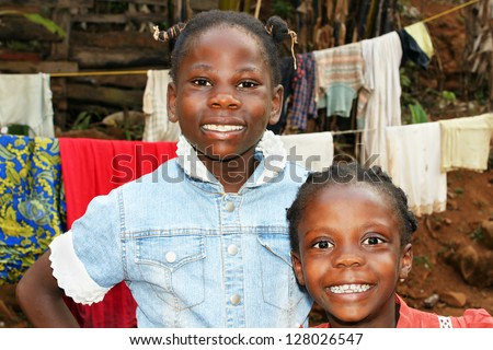 Real candid portraits of black African girls, sisters with big smiles, at home in front of clothesline in their backyard, great for future of developing countries. - stock photo