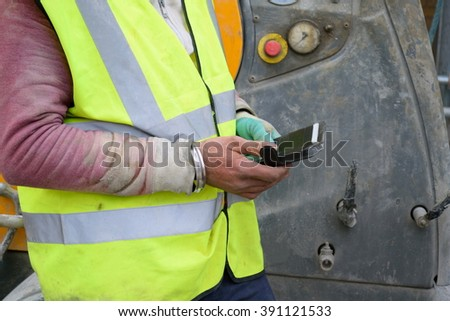 Real construction worker using mobile telephone - stock photo