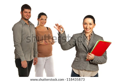 Real estate agen woman showing keys in front of happy pregnant couple isolated on white background - stock photo