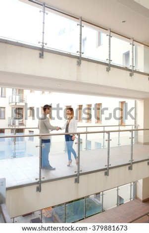 Real estate agent and customer shaking hands in corridor of apartment house. - stock photo