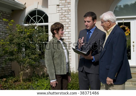 real estate agent discussing the options of a new home with potential buyers - stock photo